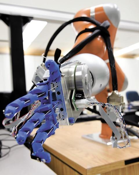 Sous la supervision du professeur Clément Gosselin, les étudiants ont développé des prototypes comme ce robot (à gauche) capable d'offrir une poignée de main de la même intensité que son utilisateur. Cette capacité pourrait notamment s'avérer très utile dans le domaine de la médecine.