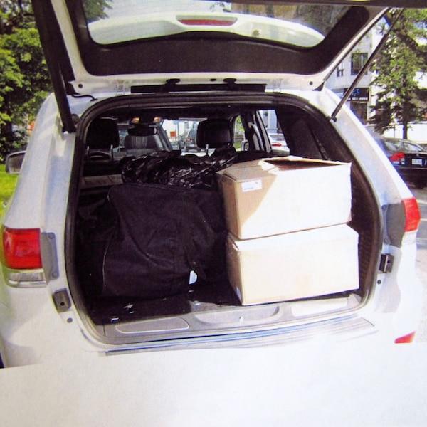Les boîtes et le sac de hockey contenant 20 kg de pot et 39720 $, saisis par les policiers.