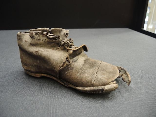 Une chaussure d'enfant (1850-1900) : De nombreuses chaussures solitaires ont été déterrées lors des fouilles réalisées au village des Tanneries. Cette petite chaussure est faite de cuir, de fer et de bois.