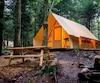 L'une des 40 tentes canadiennes tout équipées du site Huttopia Sutton et la terrasse sur le site Huttopia Sutton.