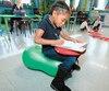 Cette élève de la classe de maternelle de Nancy Latulippe a choisi de s'asseoir sur un ballon pour faire son travail, tandis que d'autres ont choisi de s'asseoir directement au sol.