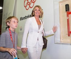 La reine des Jeux olympiques de 1976, Nadia Comaneci, pose ici avec son fils Dylan et le flambeau des Jeux de Montréal.