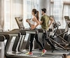 Young man and woman smiling while running side by side on electric treadmills at the gym