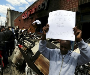 Members of the community work to clean up a recently looted and burned CVS store in Baltimore