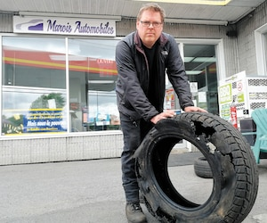 Pascal Marois, propriétaire du garage Marois Automobiles, à Saint-Basile-le-Grand, en Montérégie, montre un pneu complètement fendu. Il n'a jamais vu autant de pneus défaits dans son atelier en raison des routes désastreuses.