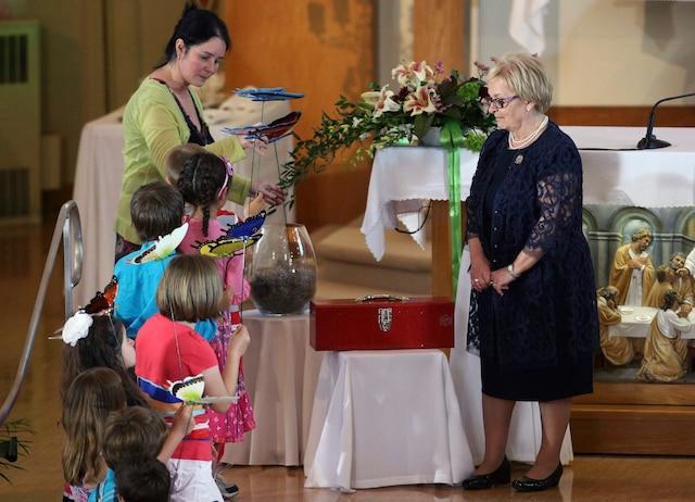 Une enfant apporte des fleurs à la mairesse de Lac-Mégantic, Colette Roy-Laroche, lors de son discours durant la messe commémorative à l'église Sainte-Agnès, à Lac-Mégantic, le 6 juillet 2014.