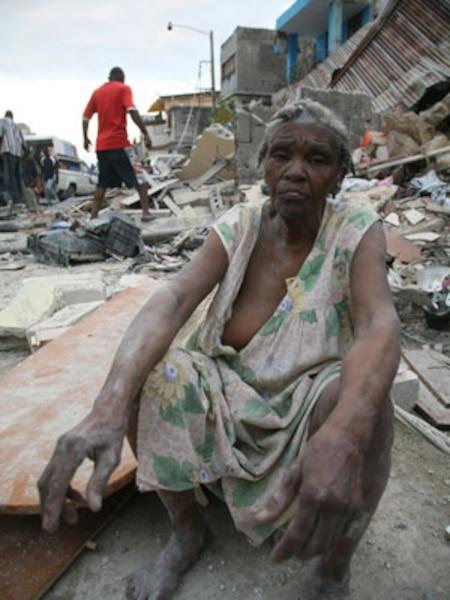 Une femme qui s'en est sortie est assise sur les débris de l'édifice qui a été complètement démoli.