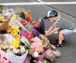 Un enfant de Christchurch dépose des fleurs en mémoire des victimes, tout près de la mosquée Al Noor où des dizaines de musulmans ont été tués.