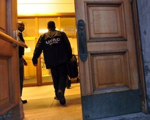 Un agent de l'UPAC entre à l'hôtel de ville.