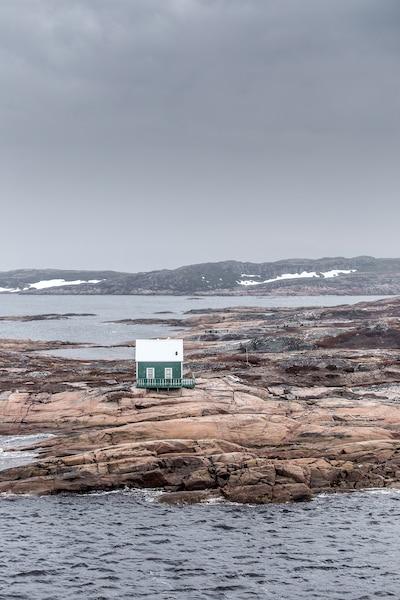 Au passage d'un chenal  étroit à l'approche  d'Harrington Harbour, une maison de pêcheur,  bâtie sur le roc, défie  les éléments.