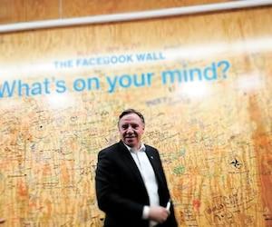 François Legault a visité, mardi, les installations de Facebook à New York. Il espère convaincre l'entreprise d'investir davantage dans ses installations de Montréal. Il a signé le mur des visiteurs où il a écrit le mot Québec à la question :What's on your mind ?