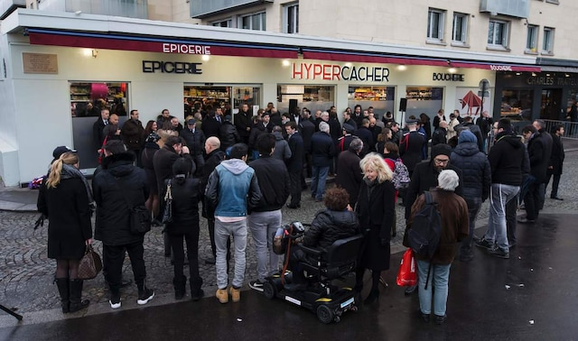 Relatives of the victims of the attack on the Hyper Cacher, a kosher supermarket, gather during a commemorative ceremony to pay tribute to the victims of the terrorist attack, on January 5, 2016 near Paris. French President Francois Hollande today kicked off a week of commemorations marking the jihadist rampage in Paris that began with an assault on satirical weekly Charlie Hebdo and lasted three days, claiming 17 lives. The president and mayor unveiled a plaque at the Hyper Cacher, in an eastern suburb where four Jews -- three shoppers and an employee -- were killed during a horrifying hostage drama. / AFP / POOL / IAN LANGSDON/POOL