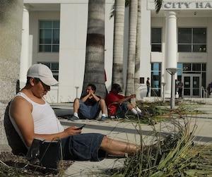 Les citoyens privés d'électricité rechargent leur téléphone cellulaire tout près de l'hôtel de ville.