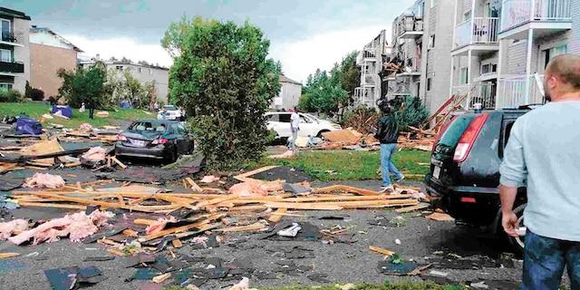 Des dizaines de citoyens s'affairaient à ramasser les débris laissés par le vortex vendredi.