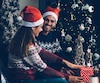 Side view of laughing couple decorating present
