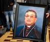 Un homme tenant le portrait de Oscar Julio Vian Morales, archevêque de Guatemala
