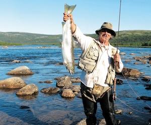 Le pêcheur André Cyr vient de capturer un saumon atlantique dans les eaux de la rivière aux Mélèzes, dans la zone visée par la privatisation de la pêche par le gouvernement libéral. Le ministre des Forêts, de la Faune et des Parcs, Luc Blanchette, a défendu cette décision, arguant qu'elle aide les Inuits à protéger leur territoire ancestral.