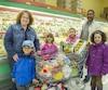 La famille Charest-Bessette de Bromont avec son panier d'épicerie débordant de fruits et de légumes, lors d'une visite bimensuelle au supermarché Kim Phat de Brossard. De gauche à droite: la mère Caroline Charest, son fils Paul, 4 ans, Anna, 6 ans, Mérylie, 10 ans, le père Kisito Bessette et Malaïka, 6 ans.