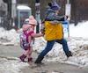Une mère et sa fille traversent unerue Atwatercouverte de gadoue, à Montréal, le 24 janvier dernier.