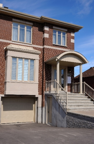 La façade du modèle D se présente avec un large porche couvert en béton. On remarque immédiatement sa généreuse fenestration.