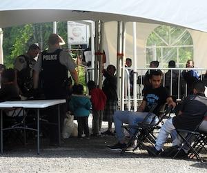 Des migrants sont pris en charge par les agents de la GRC après avoir passé la frontière à Saint-Bernard-de-Lacolle.