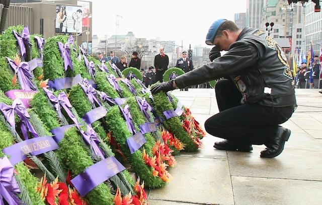 Un vétéran se recueille devant le Monument commémoratif de guerre du Canada à Ottawa.