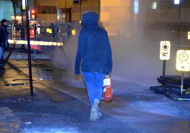 Quelques centaines d'étudiants qui s'étaient barricadés à l'intérieur des murs de l'UQAM ont été expulsés par les policiers, dans la nuit du jeudi 9 avril 2015, au centre-ville de Montréal. Sur la photo, une manifestante déambule avec un extincteur volé à l'intérieur de l'UQAM. MAXIME DELAND/AGENCE QMI