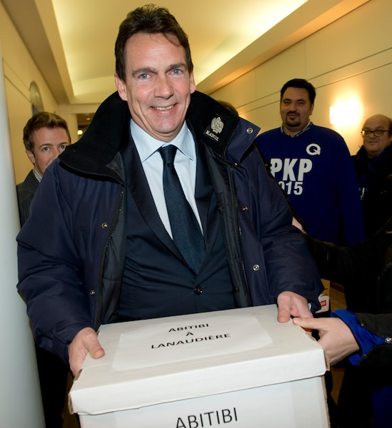 Pierre Karl Péladeau tenant une boîte de signatures de membres du Parti québécois qui appuient sa candidature.