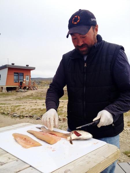 Sur les berges du lac  Manarsulik, on peut  déguster l'omble  chevalier frais sous  forme de sushi. Ici, un  guide inuit prépare  le poisson.