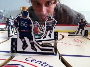 Carlo Bossio surplombant des joueurs miniatures aux uniformes à l'effigie de Hockey sur table Québec.