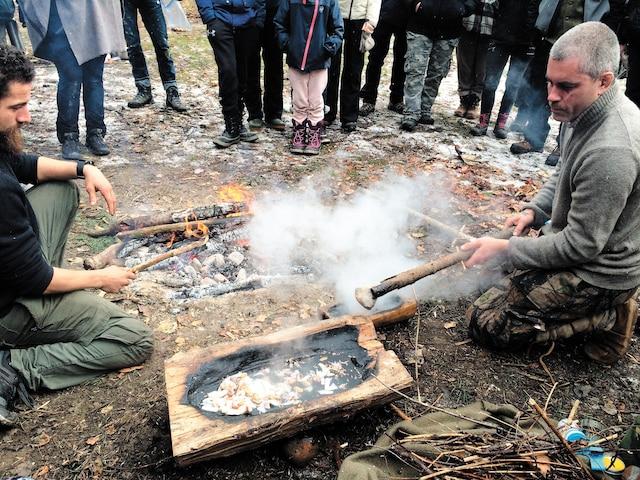 Thor Champagne et Mathieu Hébert préparent une soupe dans un bol de bois qu'ils ont fabriqué, en chauffant l'eau avec des roches brûlantes tirées du feu.