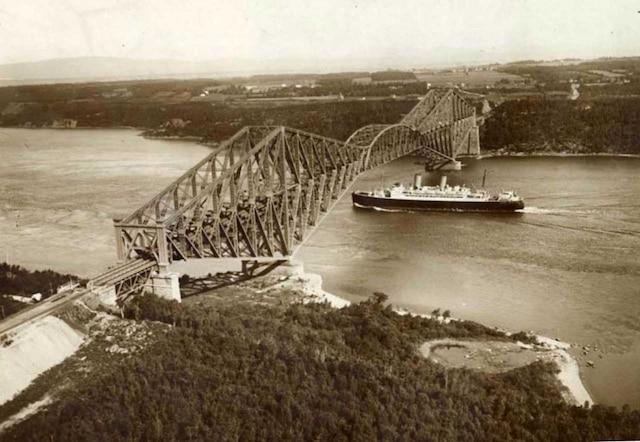 Un bateau passant sous le pont de Québec vers 1927.