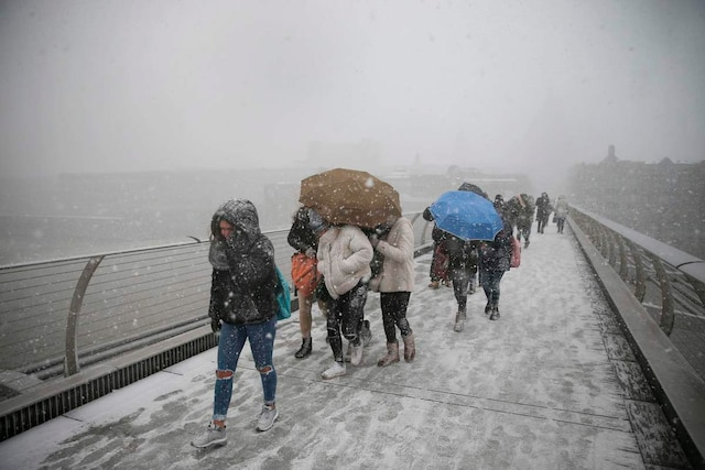 Pedestrians cross the millennium bridge as heavy snowfall hits London on February 27, 2018.  A blast of Siberian weather sent temperatures plunging across much of Europe on Tuesday, causing headaches for travellers and leading to several deaths from exposure as snow carpeted palm-lined Mediterranean beaches. / AFP PHOTO / Daniel LEAL-OLIVAS