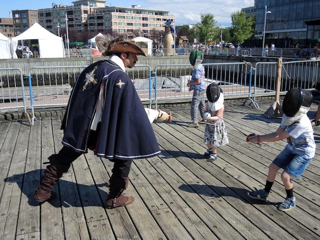 Un mousquetaire de la Garde du Lys montrait les rouages de l'escrime à l'ancienne à de jeunes apprentis, sur l'un des quais du bassin Louise.