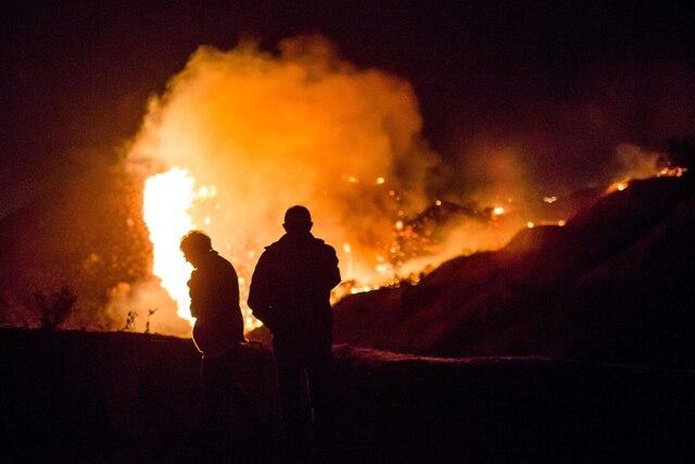 Des curieux regardent alors que les feux de forêt font rage sur une colline près des maisons du quartier Shadow Hills à Los Angeles.