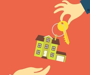 Hand real estate agent holding holds a key with a tag in the form of homes, and buyer is pulling his hands