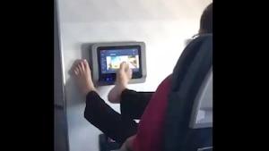 Un homme pitonne avec ses pieds sur une TV d'avion