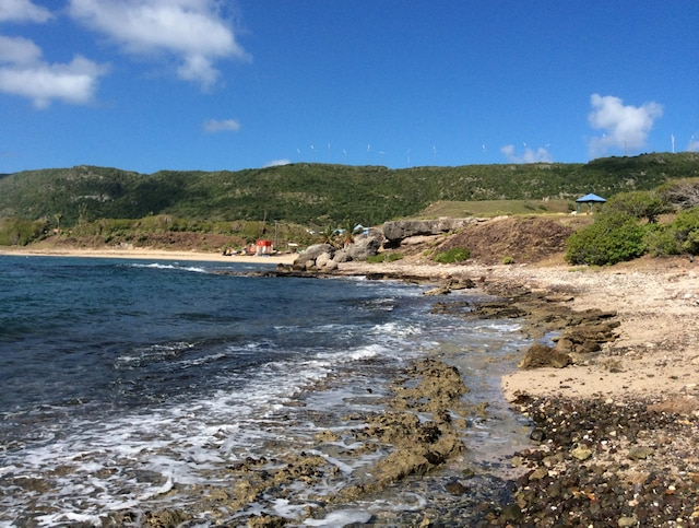 Plage rocheuse donnant sur l'océan Atlantique, Baie-Mahault, sur l'île de La Désirade. On peut voir le parc d'éoliennes sur le haut plateau. Elles ont la particularité d'être rétractables à l'approche d'un cyclone.