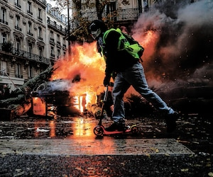 Avec sa trottinette, ce gilet jaune passe à proximité d'un des nombreux incendies allumés par des protestaires dans les rues de Paris.