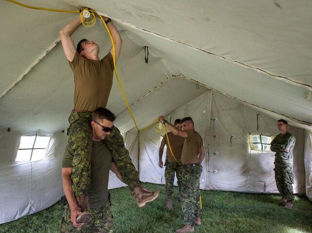 Des militaires installent l'éclairage dans l'une des tentes, qui seront aussi chauffées.