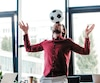 low angle view of young businessman balancing soccer ball on head in office