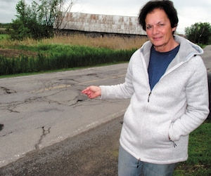 Denise Dubois montre les nombreux bris, trous et nids-de-poule en face de chez elle, sur le chemin Saint-Henri à Mascouche.