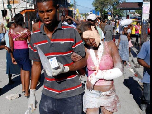 PORT-AU-PRINCE  Une femme blessée est aidée par un concitoyen alors que laide humanitaire en provenance des quatre coins du monde est en route pour Haiti.