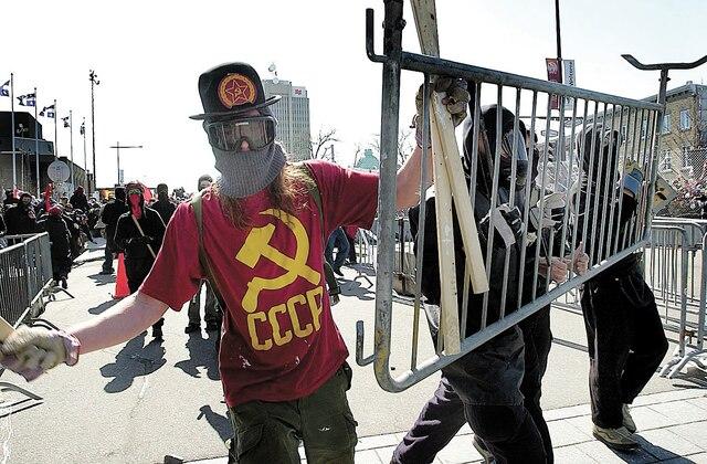 Des manifestants se protégeaient lors du Sommet des Amériques afin de faire face aux gaz lacrymogènes des policiers.