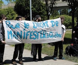 Une vingtaine de personnes se sont regroupées devant le poste de police Victoria, dimanche, en soutien à leurs confrères arrêtés durant les trois jours de manifestationsanti-G7. Sur la photo, ceux-ci tenaient une bannière revendiquant le droit de manifester.