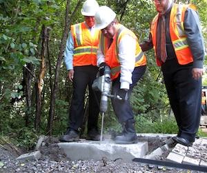 Le maire Denis Coderre s'est emparé d'un marteau-piqueur jeudi pour démolir une dalle installée par Postes-Canada afin de protester contre l'abandon du service postal à domicile.