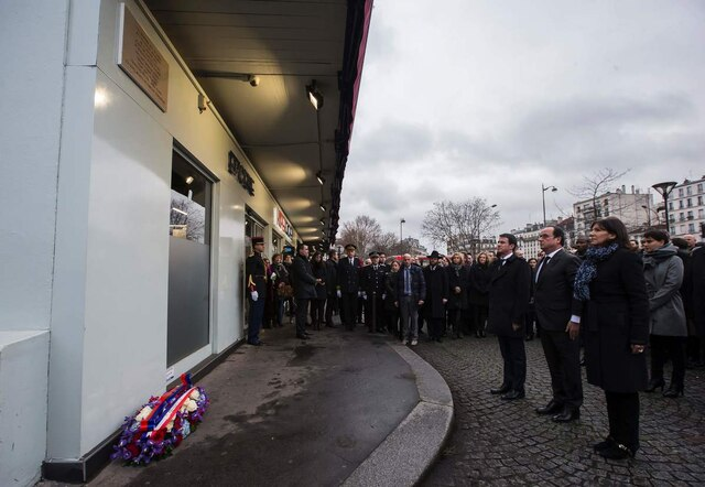 French President Francois Hollande (C), French Prime Minister Manuel Valls (3rd R) and Mayor of Paris Anne Hidalgo (R) stand at attention after unveiling in Paris on January 5, 2016 a commemorative plaque outside the Hyper Cacher, a kosher supermarket, during a ceremony to pay tribute to the victims of the attack on the supermarket on January 9, 2015. French President Francois Hollande today kicked off a week of commemorations marking the jihadist rampage in Paris that began with an assault on satirical weekly Charlie Hebdo and lasted three days, claiming 17 lives. The president and mayor unveiled a plaque at the Hyper Cacher, in an eastern suburb where four Jews -- three shoppers and an employee -- were killed during a horrifying hostage drama. / AFP / POOL / IAN LANGSDON