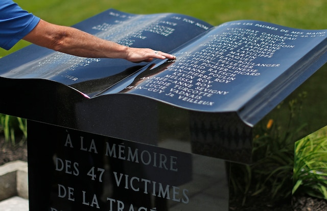 Des personnes touchent le monument en hommage aux victimes de la tragédie de Lac-Mégantic, à la suite de la messe commémorative à l'église Sainte-Agnès.