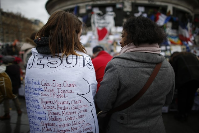A woman wearing a jacket reading the names og the January 2015 and November 2015 Paris attacks victims is pictured on Place de la Republique (Republic square) on January 10, 2016 in Paris, as the city marks a year since 1.6 million people thronged the French capital in a show of unity after attacks on the Charlie Hebdo newspaper and a Jewish supermarket. Just as it was last year, the vast Place de la Republique is the focus of gatherings as people reiterate their support for freedom of expression and remember the other victims of what would become a year of jihadist outrages in France, culminating in the November 13 coordinated shootings and suicide bombings that killed 130 people and were claimed by the Islamic State (IS) group.  AFP PHOTO / THOMAS SAMSON