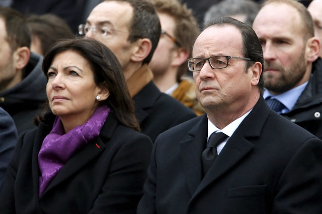 French President Francois Hollande (R) and Paris Mayor Anne Hidalgo attend a ceremony at Place de la Republique square to pay tribute to the victims of last year's shooting at the French satirical newspaper Charlie Hebdo, in Paris, France, January 10, 2016. France this week commemorates the victims of last year's Islamist militant attacks on satirical weekly Charlie Hebdo and a Jewish supermarket with eulogies, memorial plaques and another cartoon lampooning religion.  REUTERS/Charles Platiau